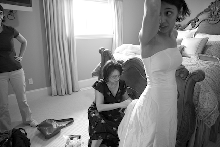 Aminah looks at her reflection in the bathroom mirror while her mother fits the dress and her aunt looks on.